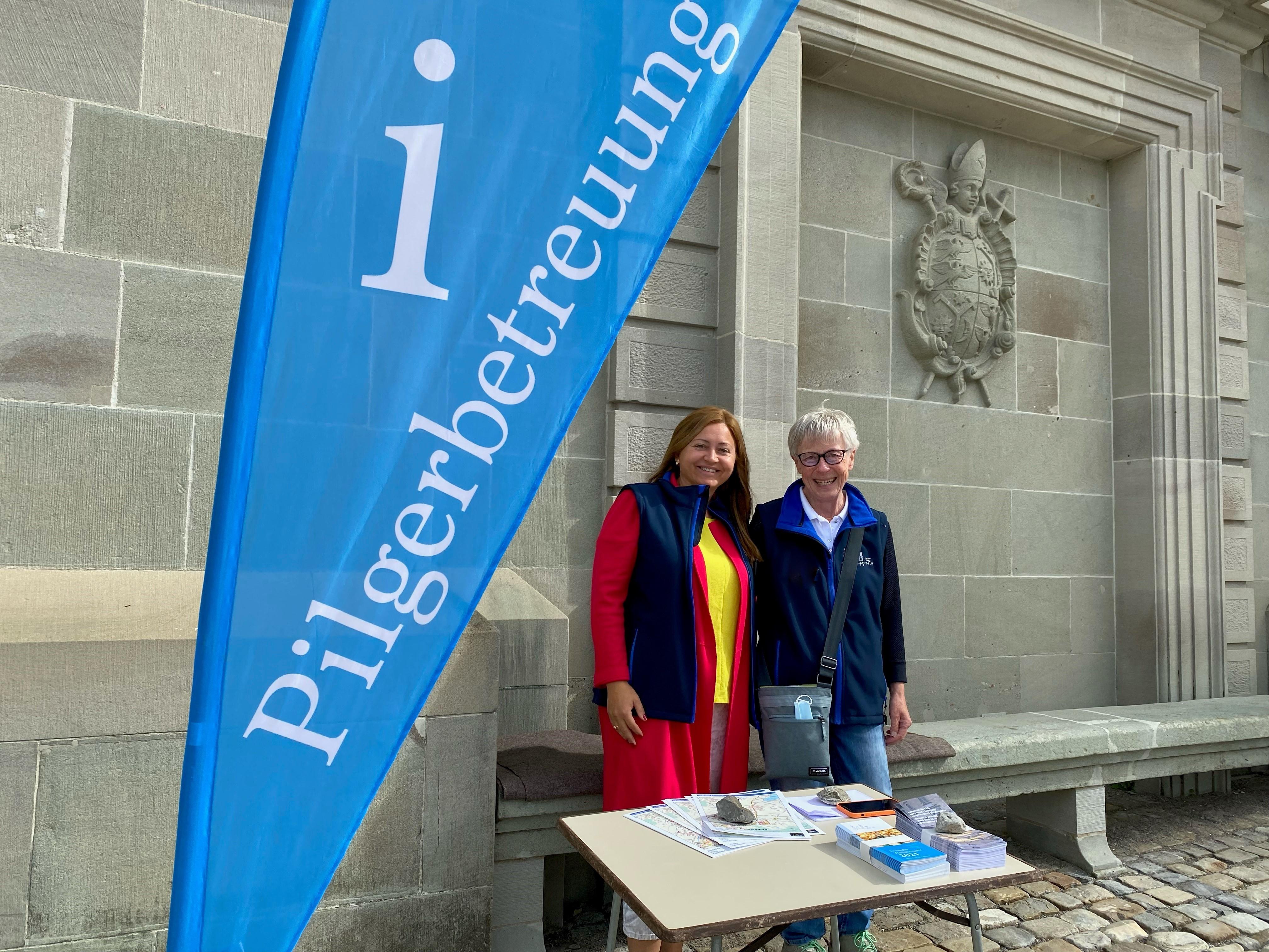 Zwei freundliche Pilgerbetreuerinnen vor der Klosterkirche. Seit Kurzem weist eine Fahne auf das Angebot der Pilgerbetreuung hin. Die Frauen und Männer sind jeweils zu zweit im Einsatz.